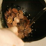 Pennies being washed in a colander