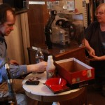 A man and a woman use a penny press