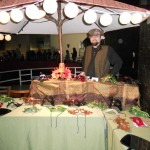 A table covered with leather maks, under a large umbrella with lanterns. A man with goblin ears stands behind the table.