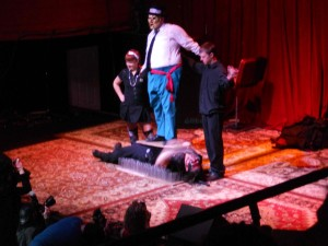 a man lies on his back on a bed of nails while another man in a mask stands on his chest