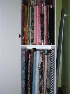 fabric on bolts stored on shelves in stand alone closet